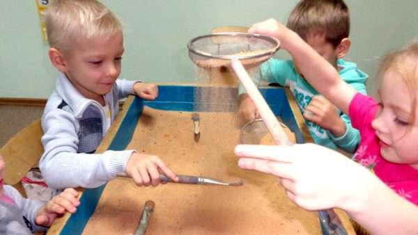 Дети просеивают песок через сито и работают с кисточками