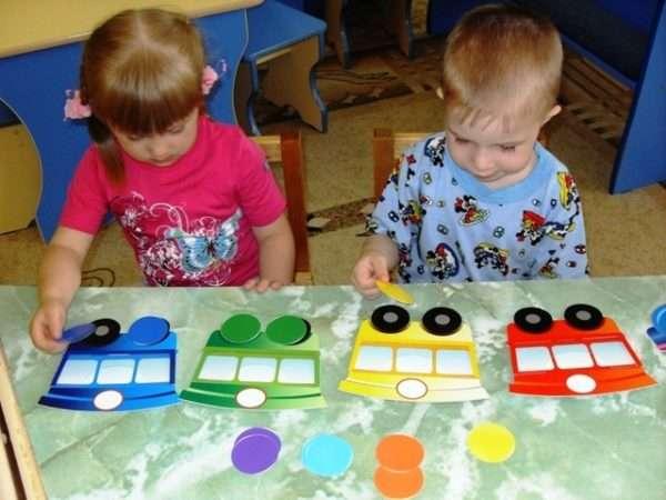 Девочка и мальчик закрывают цветными кругами колёса разноцветного картонного поезда