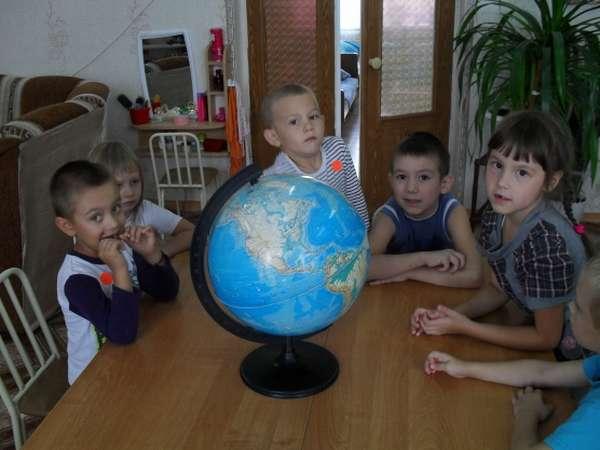 Дети сидят за столом вокруг глобуса