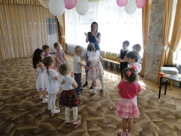 Дети стоят вокруг воспитательницы и хлопают в ладоши