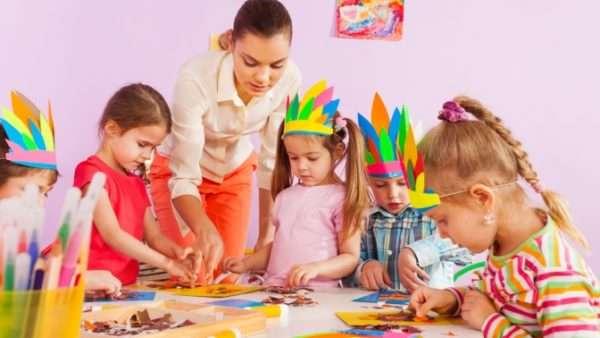Педагог и дети делают из бумаги головные уборы индейцев