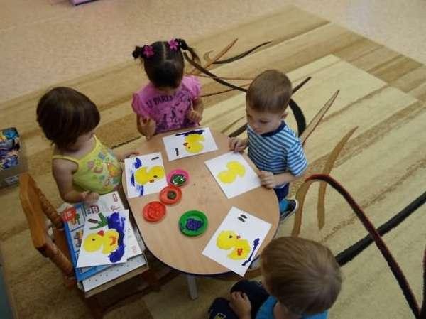 Четверо детей сидят за овальным столиком и рисуют цыплят