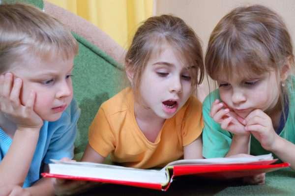 Две девочки и мальчик читают книгу