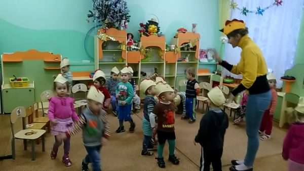 Воспитательница в шапочке курочки, дети в шапочках цыплят
