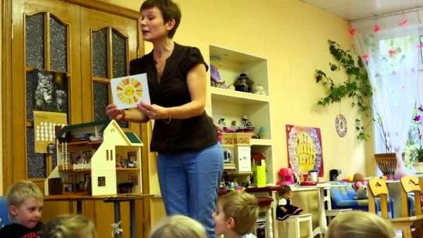 Воспитательница показывает детям картинку с изображением солнца