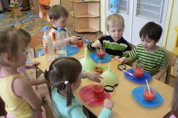 Дети разводят краску в стаканчиках с водой