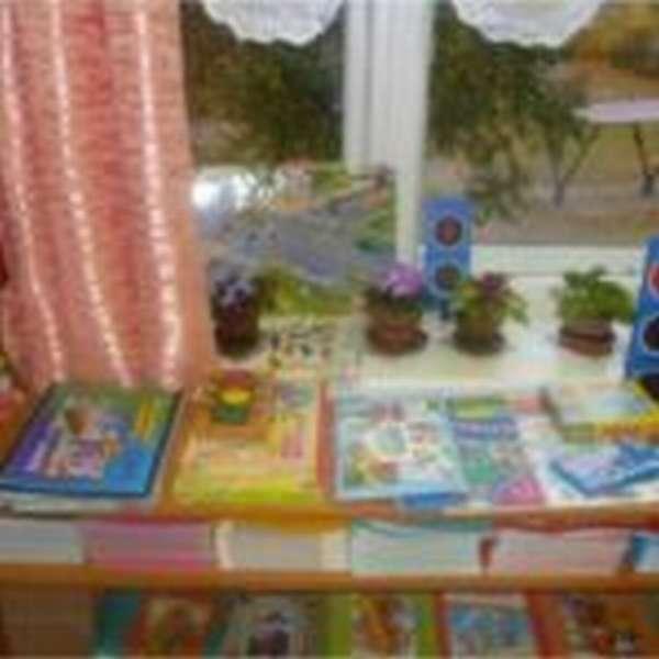 На столе разложены настольно-печатные игры, под столешницей — стопки прописей
