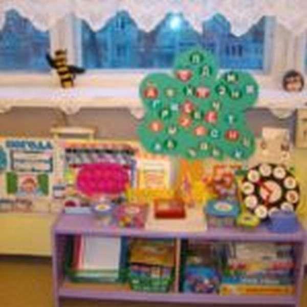 Фиолетовый стеллаж с играми и картонным деревом с буквами