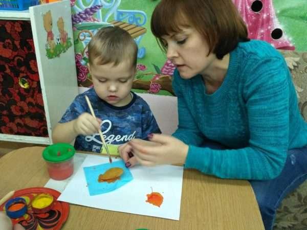 Педагог помогает мальчику делать отпечатки листьев на бумаге