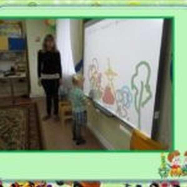 Мальчик рисует на интерактивной доске, воспитатель стоит рядом
