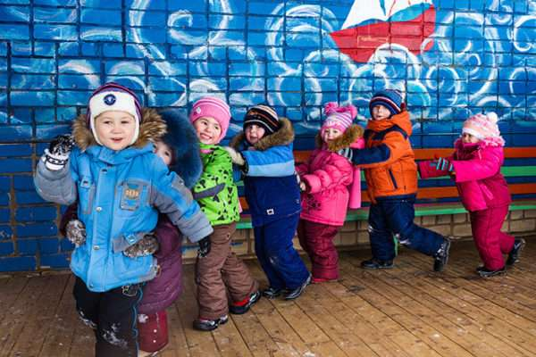 Дети в тёплой одежде идут паровозиком