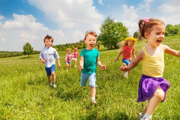 Дети куда-то бегут по траве