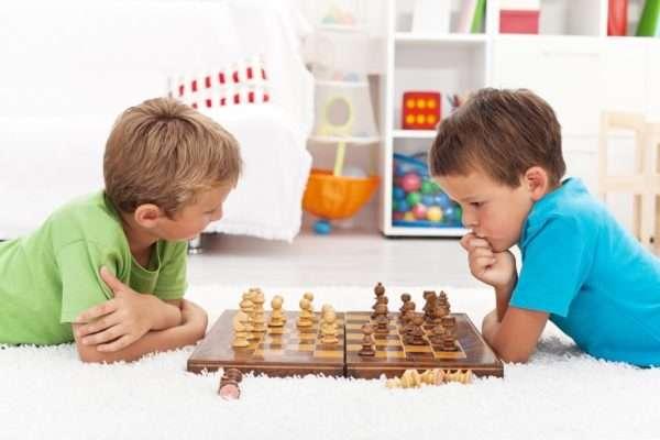 Два мальчика играют в шахматы на полу и размышляют