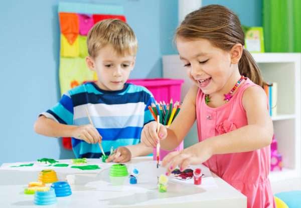 Мальчик и девочка рисуют красками