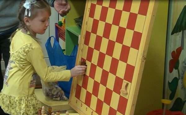Девочка играет с магнитной доской, к которой крепятся шахматы