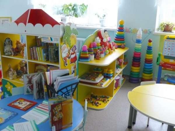Детская мебель с игрушками, книгами на полках, справа стол из двух полуокружностей