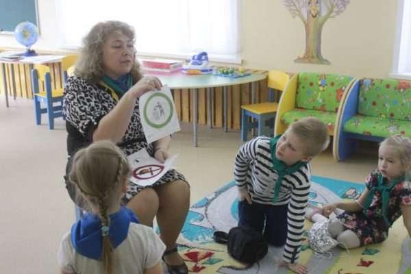 Воспитательница показывает детям экологические знаки