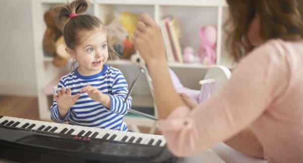 Девочка повторяет движения пальчиками за педагогом
