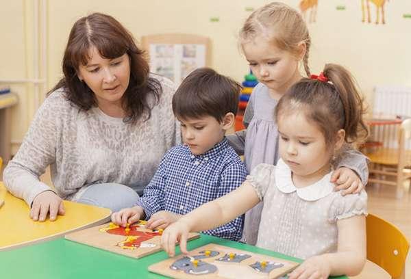 Воспитательница и девочка смотрят, как двое детей складывают пазл