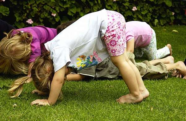 Дети на лужайке стоят на четвереньках
