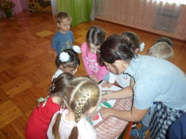 Дети с воспитательницей делают совместную аппликацию