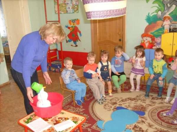 Воспитатель показывает детям снеговика, стоящего в тазу в группе