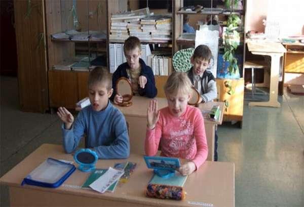 Дети, сидя за партами, занимаются биоэнергопластикой