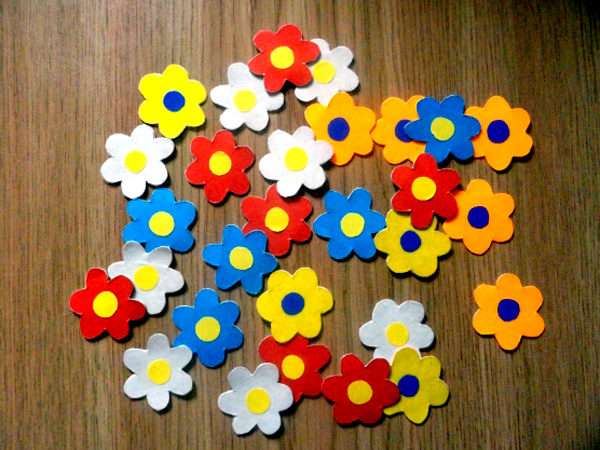 Разноцветные цветочки, сделанные из картона, лежат на столе