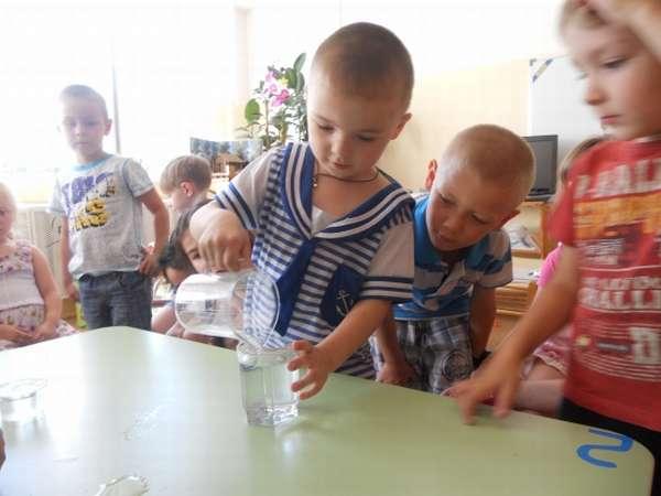 Дети проводят опыт «Имеет ли форму вода?»