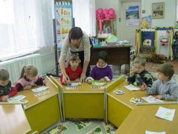 Дети рисуют красками, педагог помогает девочке