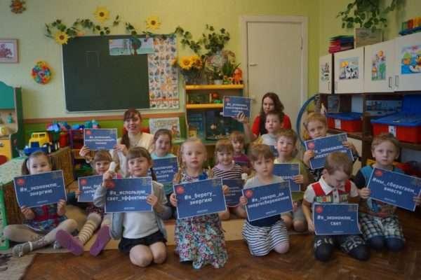 Дети и педагоги держат в руках листы бумаги с фразами, посвящёнными энергосбережению