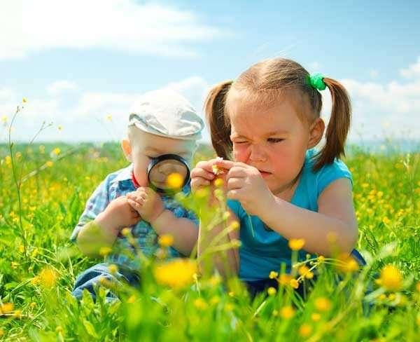 Мальчик и девочка рассматривают цветы на лугу