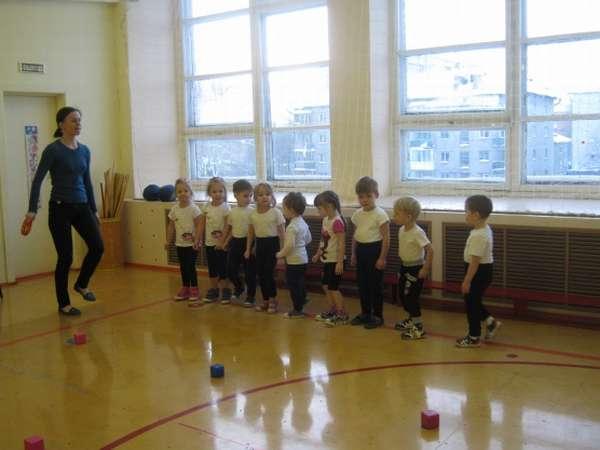 Педагог показывает упражнение детям, стоящим в шеренге