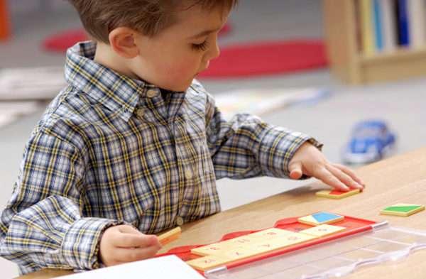 Мальчик складывает мозаику с цифрами на квадратах