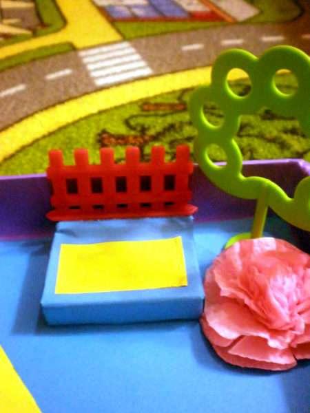 Лавочка из спичечного коробка, рядом пластмассовое дерево и бумажный цветок