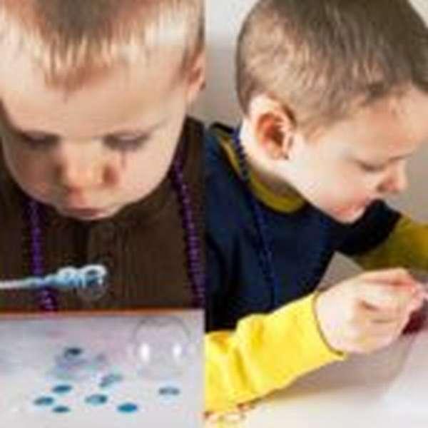 Два мальчика рисуют мыльными пузырями