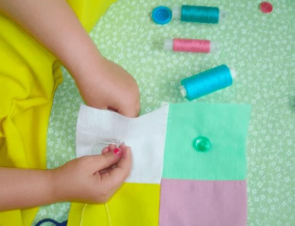 Девочка пришивает пуговицу