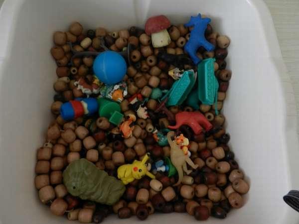 Коричневые бусины и маленькие игрушки в белом лотке