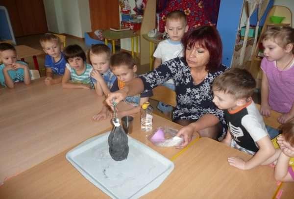 Дети и воспитатель наблюдают за самостоятельно изготовленным макетом вулкана