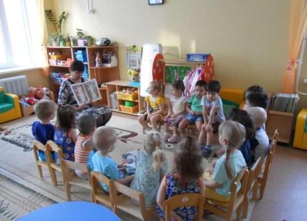 Воспитатель показывает детям разворот книги