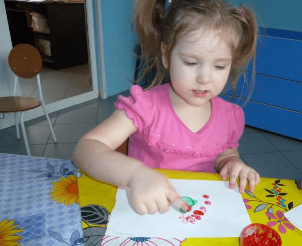 Девочка рисует пальчиковыми красками