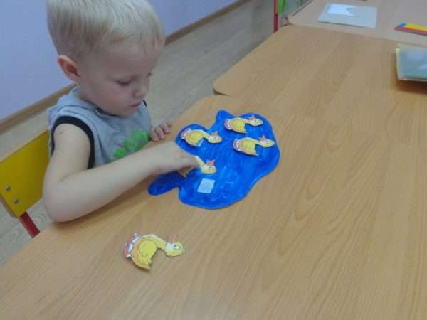 Мальчик клеит уточек на вырезанный из бумаги пруд