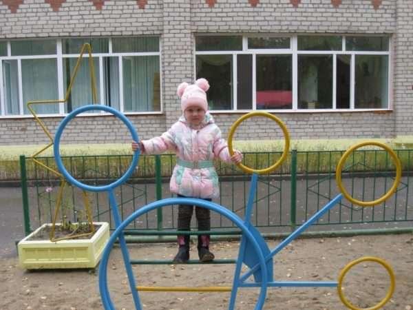 Девочка на турнике перед зданием детского сада
