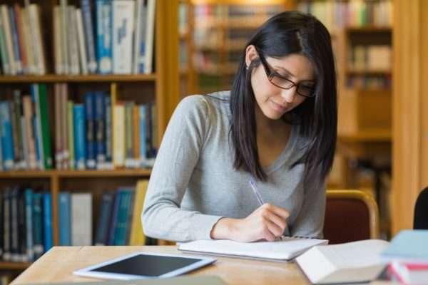 Женщина сидит за столом в библиотеке и записывает что-то в тетради