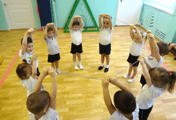 Дети стоят в кругу с поднятыми руками и держат верёвочку