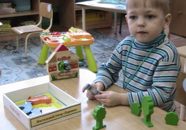 Мальчик играет с персонажами настольного театра