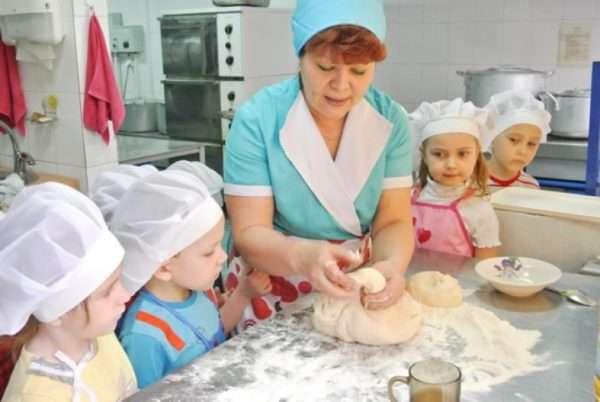 Малыши наблюдают, как повар замешивает тесто