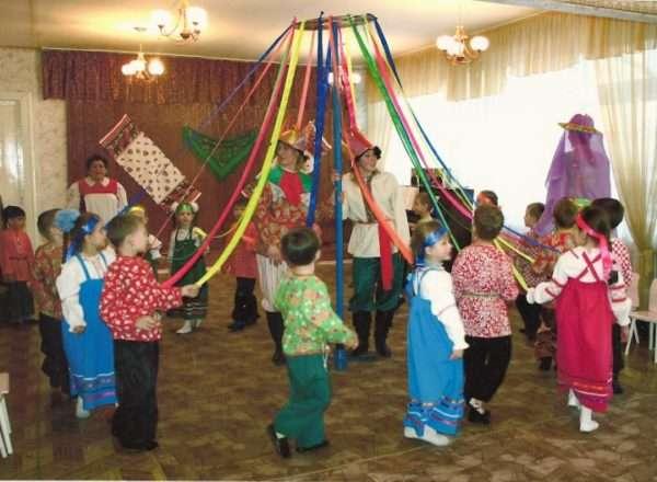 Дети и педагоги в костюмах отмечают Масленицу