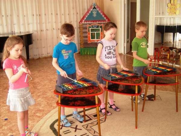 Четыре ребёнка играют на музыкальных инструментах — металлофонах и треугольнике