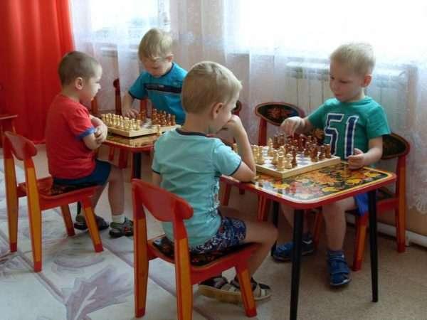 Две пары детей играют в шахматы